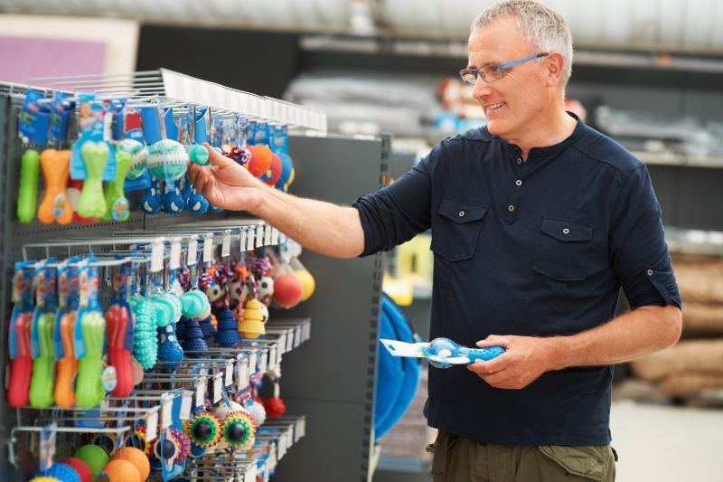 A man in a blue shirt shops for pet toys to help shelter animals.